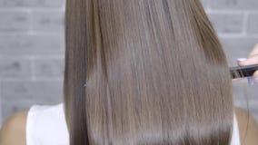 Resultado após a laminação e o cabelo que endireitam em um salão de beleza para uma menina com cabelo marrom Conceito dos cuidado filme