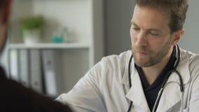 Resultado masculino atento del examen médico de la lectura del doctor y vitaminas que prescriben almacen de metraje de vídeo