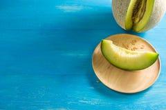 Resultados do melão Localizado nas tabelas de madeira azuis e reparta uma parte na bacia de madeira de Brown fotos de stock