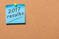 2017 resultados mandan un SMS en una nota azul fijada en el tablero del corcho con el espacio vacío para el texto Comentario del  Fotografía de archivo