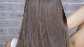 Resultat efter lamination och hår som rätar ut i en skönhetsalong för en flicka med brunt hår Begrepp f?r h?romsorg stock video