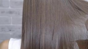 Resultat efter lamination och hår som rätar ut i en skönhetsalong för en flicka med brunt hår Begrepp f?r h?romsorg arkivfilmer