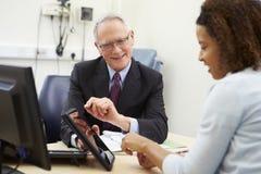 Resultat för doktor Showing Patient Test på den Digital minnestavlan royaltyfri fotografi