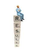 Results. Businssman sitting on the word results stock images