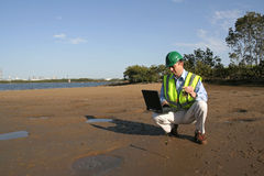 The results are in. An environmental engineer, wearing protective clothing about to examine pollution results on his laptop, from the mudflats in the estuary Royalty Free Stock Image