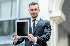Results. Successful businessman in formal wear holding a tablet Stock Image