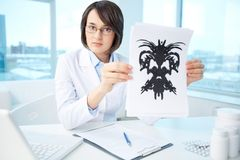 Results of test. Serious psychologist showing paper with Rorschach inkblot Stock Image