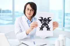 Results of test. Serious psychologist showing paper with Rorschach inkblot Royalty Free Stock Photography