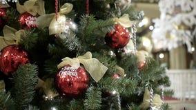 Resuma el fondo borroso de la alameda de compras con las decoraciones de la Navidad Oro y bolas rojas con el viento almacen de video