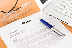 Resume with Pen by Laptop Stock Image