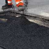 Resurfacing the road. A closeup of asphalt being poured onto the road as a worker uses a fork to even it out Stock Photo