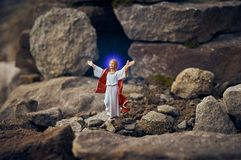 Resurrected Jesus Christ standing in front of the entrance to the grave - tomb. He stands among the rocks. Resurrected Jesus Christ standing in front of the stock photos