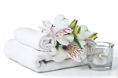 Resurser för brunnsort, den vita handduken, stearinljus och blomma Royaltyfri Foto