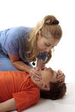 Resuscitation. A nurse performing mouth to mouth resuscitation to a child in an emergency Stock Image