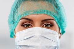 Resuscitation and emergency concept. Female doctor's face wearing protective mask and green surgeon's cap closeup. Surgeon's eyes close up gazing intently in Royalty Free Stock Photo