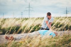 Resuscitation on the road. Young men calling for Emergency medical service. Dramatic resuscitation on the rural road. Themes rescue, help and hope Royalty Free Stock Photography