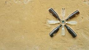 Resused flaskor dekorerade på den skrovliga leraväggbacgrounden av th Arkivbild