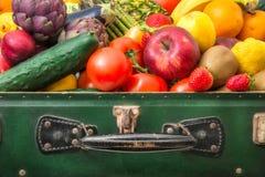 Resväska mycket av frukt och grönsaker royaltyfri bild