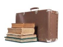 Resväska och bok Arkivfoto