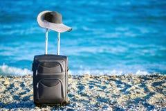 Resväska och hatt på stranden royaltyfri foto