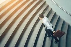 Resväska och spring för affärsman hållande på trappa royaltyfria bilder