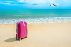 Resväska på den soliga stranden royaltyfri bild
