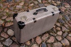 Resväska på kullerstenstenen royaltyfri fotografi