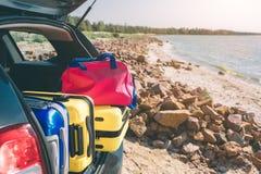 Resväskor och påsar i stammen av bilen som är klar att avgå för ferier Flyttande askar och resväskor i stam av bilen, utomhus royaltyfri bild
