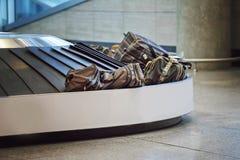 Resväskor på ett bagage sätter band på flygplatsen royaltyfria bilder
