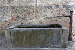 Retângulo velho bem com água corrente da torneira da fonte em Glurn fotografia de stock