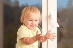 Retén adorable de la muchacha en el travesaño de la ventana Fotografía de archivo