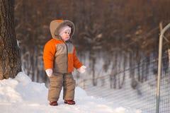 Retén adorable del bebé cerca de la cerca de la protección del esquí Imagenes de archivo