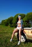 Retén atractivo joven de la mujer cerca del coche retro imagen de archivo libre de regalías