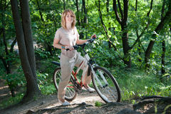 Retén de la muchacha con una bicicleta imagen de archivo
