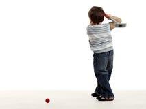 Retén del muchacho detrás y preparándose para golpear una pelota de golf Fotos de archivo libres de regalías