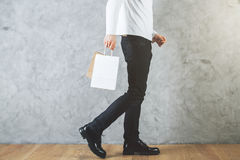 Retail concept. Side view of man`s legs and empty shopping bag in hands in room with concrete wall and wooden floor. Retail concept. Mock up royalty free stock image