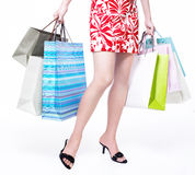 Retail consumerism. Sexy legs with shopping bags. Waist-down closeup view of woman carrying shopping bags with both hands. Studio shot isolated on white Stock Photos