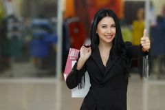 Retail, gesture and sale concept - smiling woman with many shopping bags showing thumbs up. Stock Photography