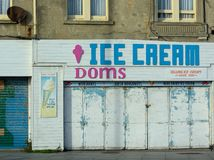 Retail Ice Cream shop closed with metal shutters. A coastal town retail shop selling ice cream closed and locked up for winter stock images