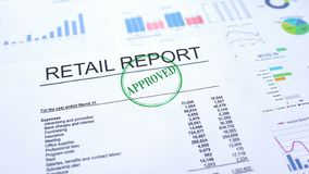 Retail report approved, hand stamping seal on official document, statistics. Stock photo stock photography