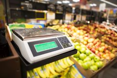 Retail Store Fruits Weighing. Retail Store Electronic Weighing Scales and the Store Fresh Products in the Background royalty free stock photos