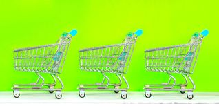 Retail store shopping concept. Miniature shopping carts on green screen stock photography