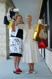 Retail Therapy. Two senior women shopping together having fun holding up lots of shopping bags Royalty Free Stock Photos