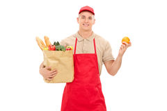 Retail worker holding an orange and a grocery bag. Isolated on white background stock images