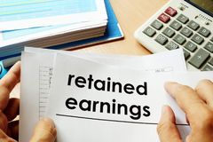 Retained earnings concept. Papers with title retained earnings Stock Images
