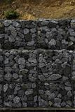 Retaining stone wall next to the road. Protection fence or wall made of gabions with stones. Stone wall with metal grid as backgro. Und. stone floor texture, A stock image