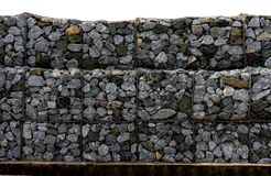 Retaining stone wall next to the road. Protection fence or wall made of gabions with stones. Stone wall with metal grid as backgro. Und. stone floor texture, A stock photography
