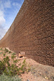Retaining wall. Vertical image of a wire mesh and loose rock retaining wall with drain pipe perspective view stock photo