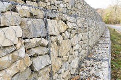 Retaining wall gabion. Retaining drywall, built of stone filling a container made from a wire mesh hexagonal mesh, said gabion Stock Photos