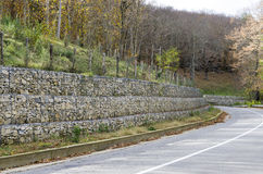 Retaining wall gabion. Retaining drywall, built of stone filling a container made from a wire mesh hexagonal mesh, said gabion Stock Photography